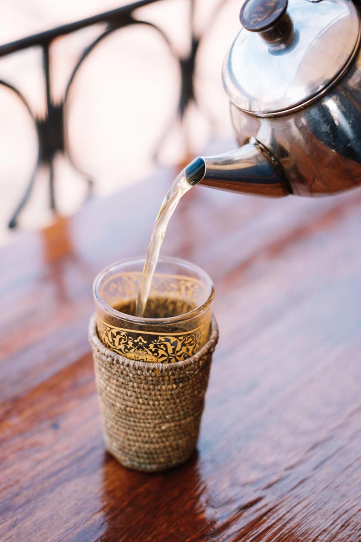 Tee wird auf der Dachterrasse eines Cafes in Marrakesch eingeschenkt.