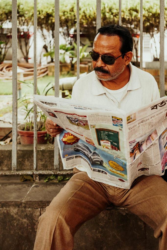 Mann liest Zeitung auf der Straße, Sightseeing in Kolkata mal anders.