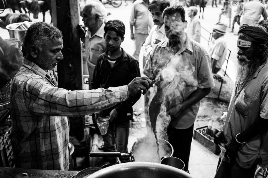 Indischer Chai, der Masala Chai in Varanasi. Die Zubereitung ist eine Kunst für sich, bei der der Chai mit Milch ständig kunstvoll umgewälzt wird.
