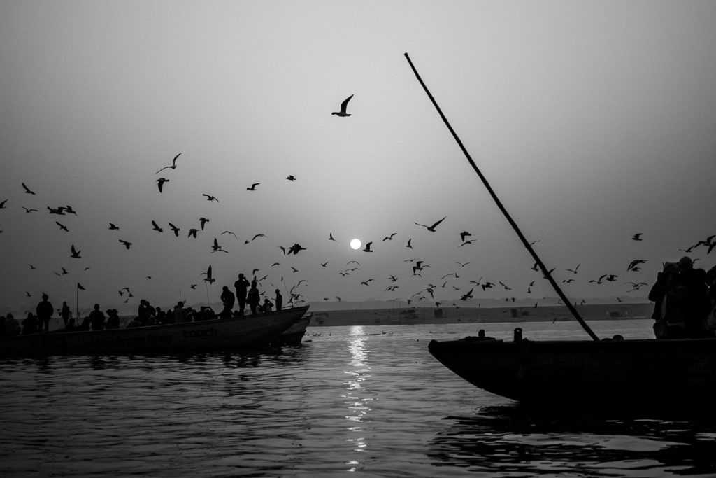 Sonnenaufgang in Varanasi am Ganges. Vögel und Boote begrüßen den Tag.