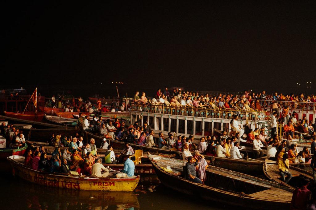Viele Menschen versammeln sich am Ganges, um dem Aarti Ritual am Ghat in Varanasi beizuwohnen.