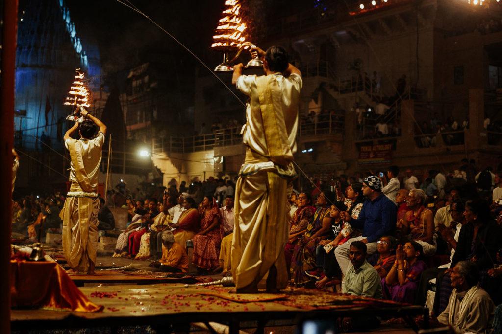 Religionsgelehrte schwenken große Feuerlampen während des Aarti Rituals in Varanasi.
