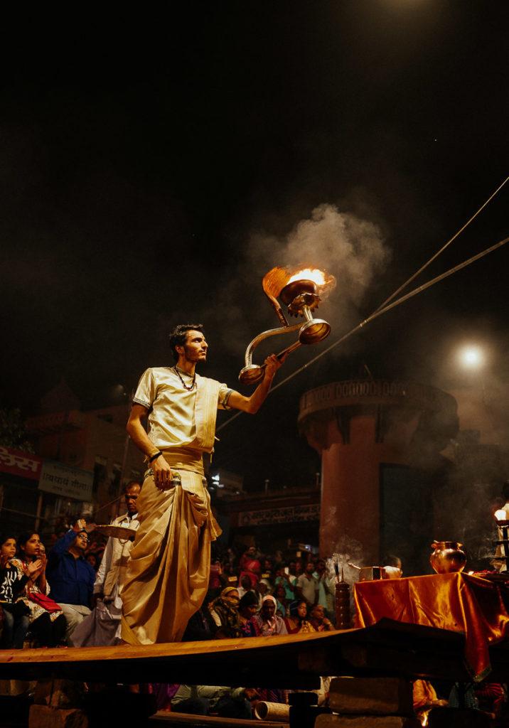 Ein Religionsgelehrter schwenkt eine große Feuerlampe zu Ehren des Aarti Rituals.