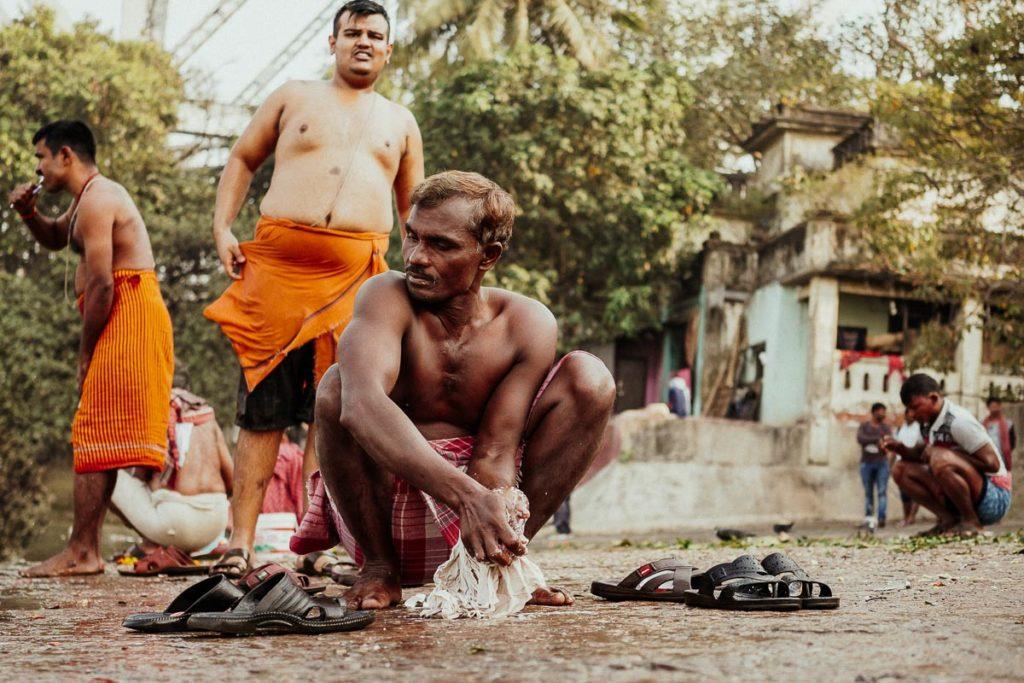 Wäsche waschen und Zähne putzen am Fluss Hugli in Kolkata.
