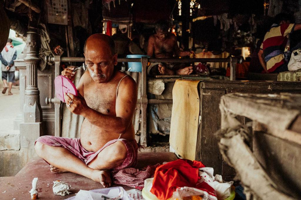 Blumenmarkt am Fluss Hugli in Kolkata. Ein Mann bei der morgendlichen Rasur.