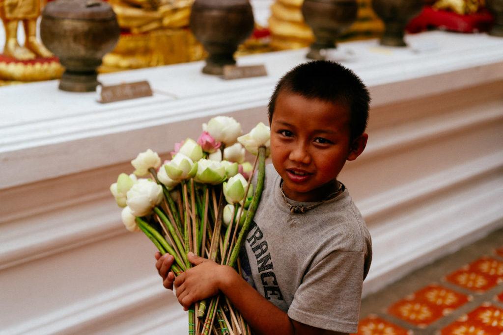 Junge mit Blumen im Tempel Doi Suthep