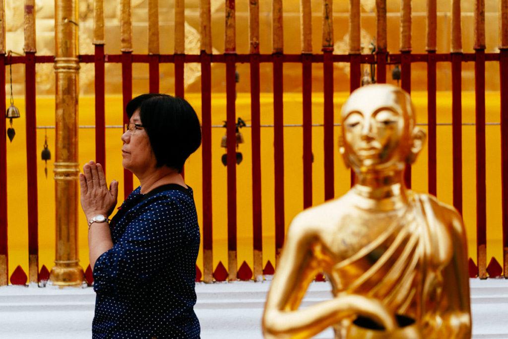 Betende Besucherin und Buddha-Statue im Wat Phra That Doi Suthep