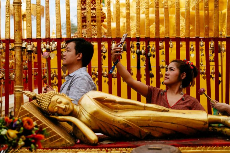 Beten und Selfies: Besucher des Wat Phra That Doi Suthep beten nach vorgegebenen Ritual oder machen Fotos von sich und dem Temepl. Im Vordergrund eine liegende Buddha-Statue