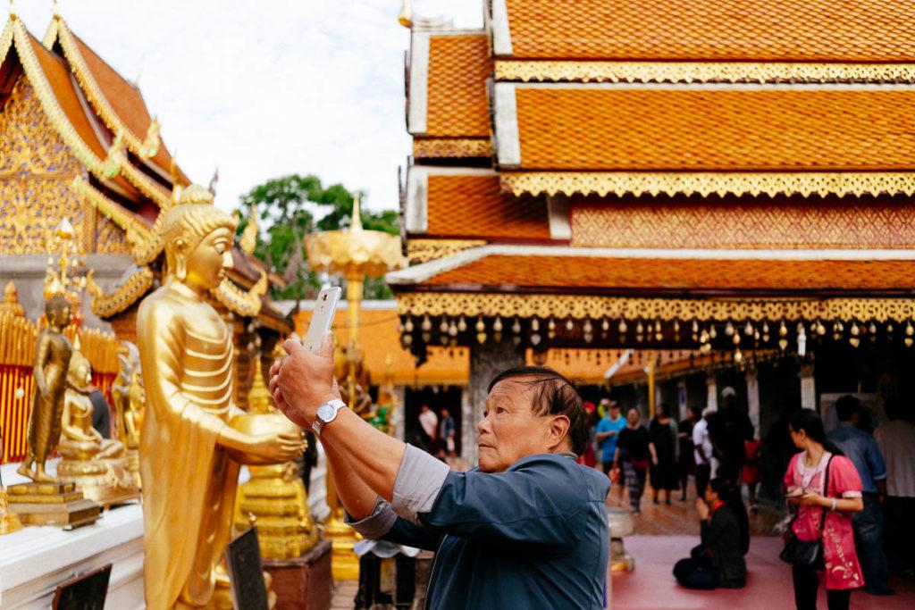 Besucher fotografieren die vielen Buddha-Statuen im Tempel Doi Suthep