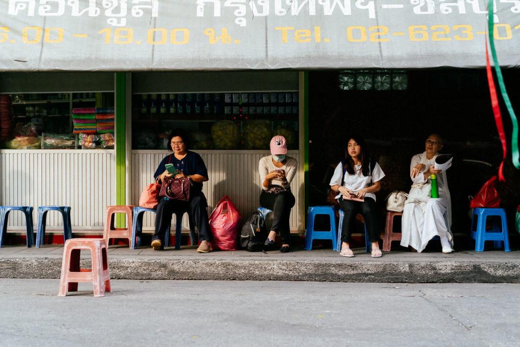 Typische Szene in Chinatown: Menschen sitzen auf kleinen Plastikstühlen vor einem Laden in Chinatown