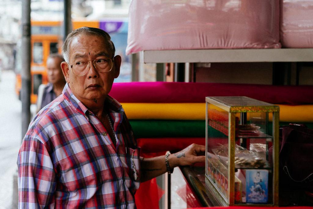Stofffachhandel in Bangkok, ein Mann schaut argwöhnisch auf die Straßen von Chinatown