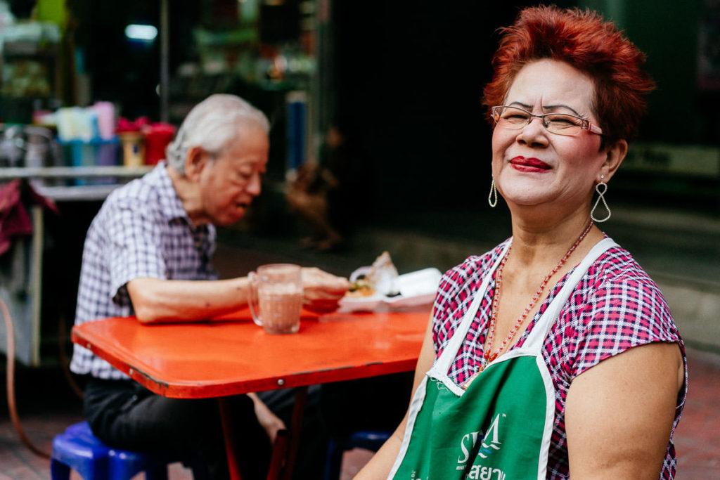 Straßenverkäuferin in Chinatown mit weißender Creme im Gesicht und auffälligem Make-up