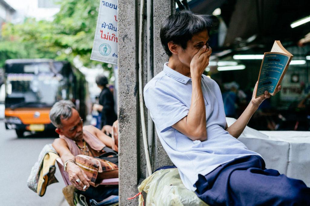 Ein gutes Buch und Mittagspause. Zwei Männer sitzen am Straßenrand in Chinatown, einer liest ein Buch, dass ihn mitreißt. Der andere macht ein Schläfchen.