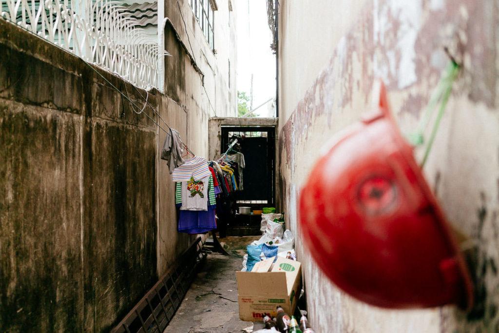 Blick in schmale Gasse in Bangkok mit Gerümpel, im Vordergrund ein roter Helm