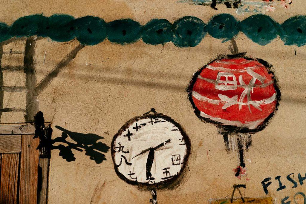 Wandmalerei in Talat Noi von einem Lampion und einer Uhr.