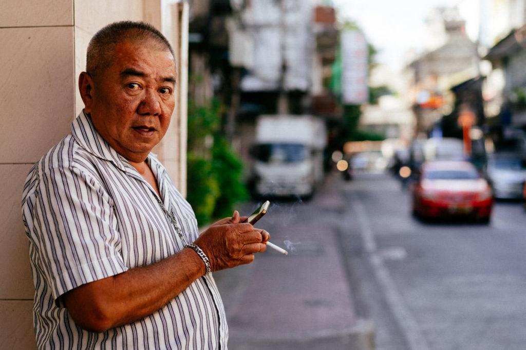 Einheimischer in Bangkok mit Handy und Zigarette in den Händen