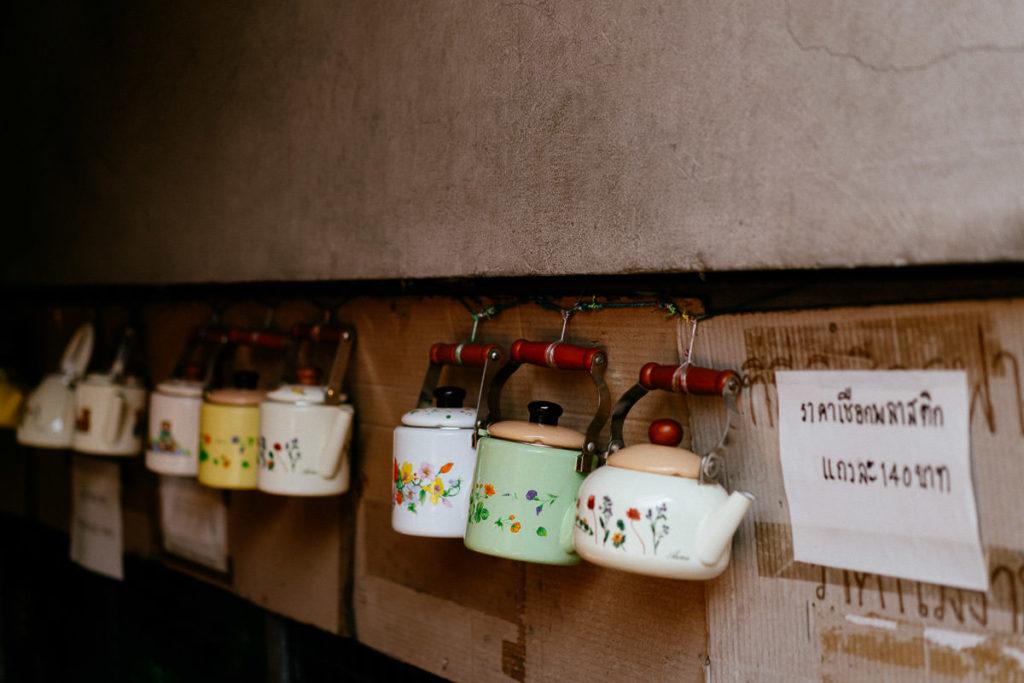 Kleine Wasserkessel in bunten Farben hängen zum Verkauf an einer Wand in Bangkok
