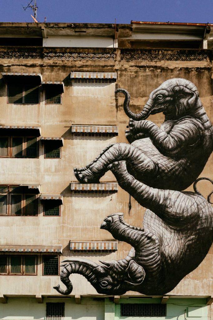 Wandmalerei in Talat Noi in Bangkok. Es zeigt zwei Elefanten, die turnen, an einer Hauswand.