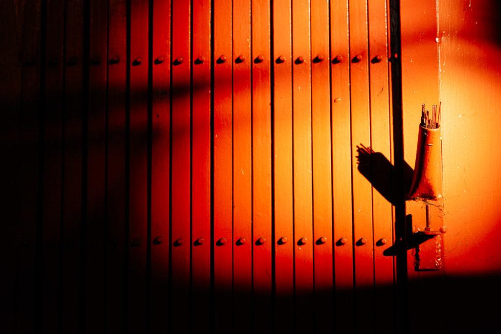 Rote Wand wird von Sonne beschienen, an der rechten Seite sind Räucherstäbchen befestigt.