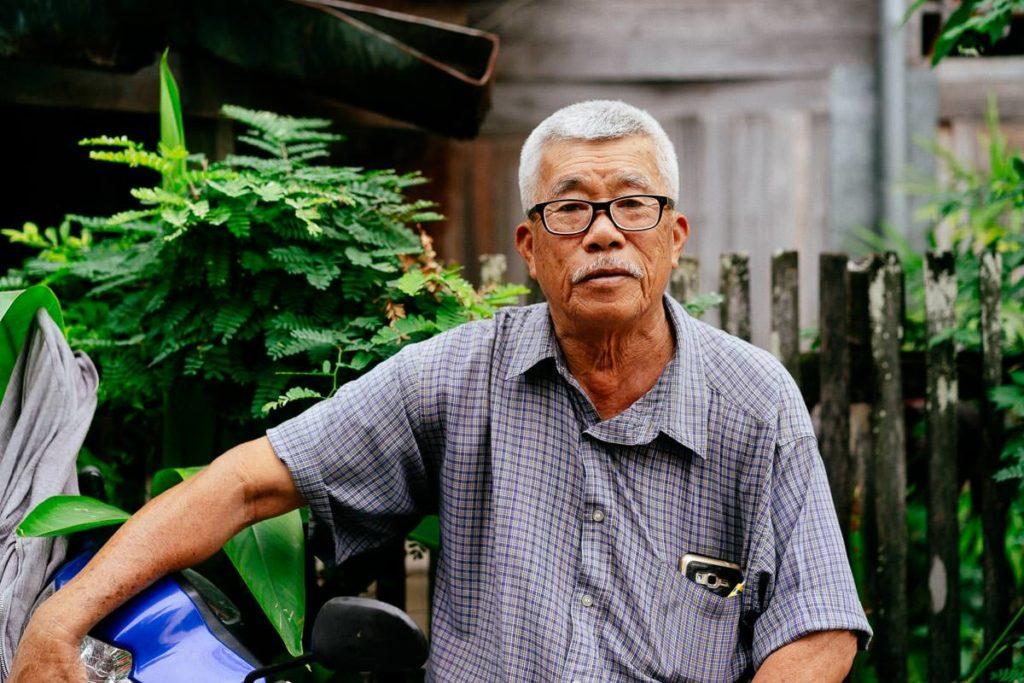 Mann mit seinem Moped in einer Nebenstraße in Chiang Mai
