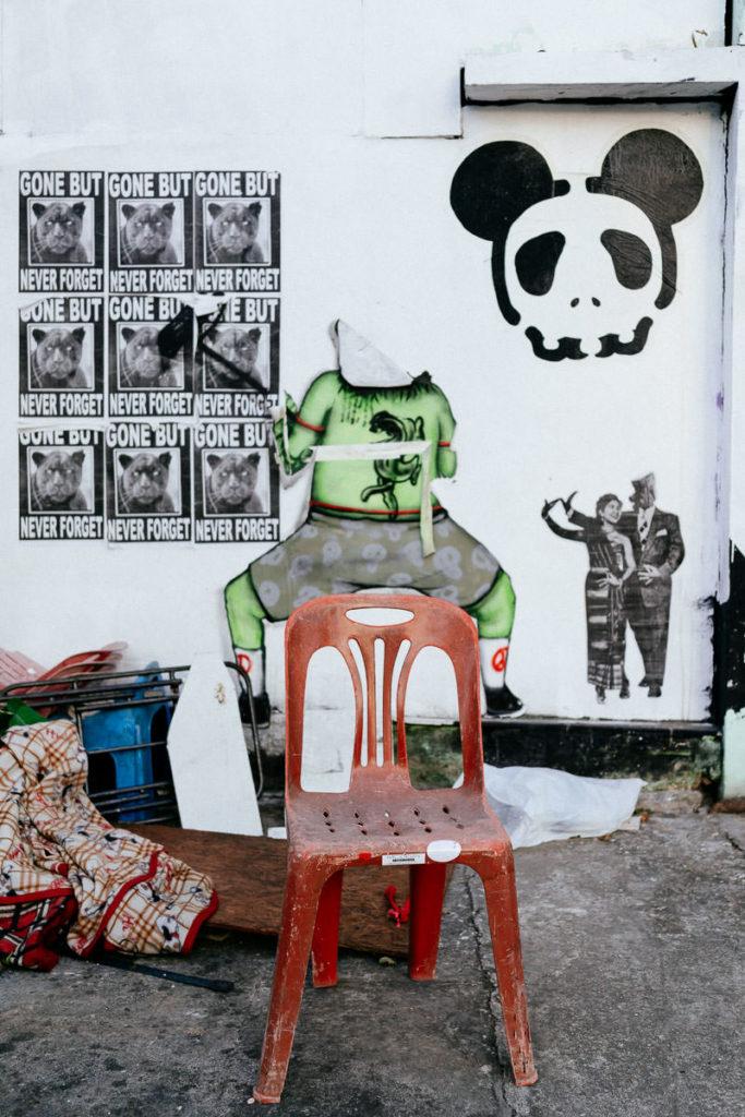 Roter Stuhl und Gerümpel vor einer Wand mit Werbung und skurrilen Graffitis