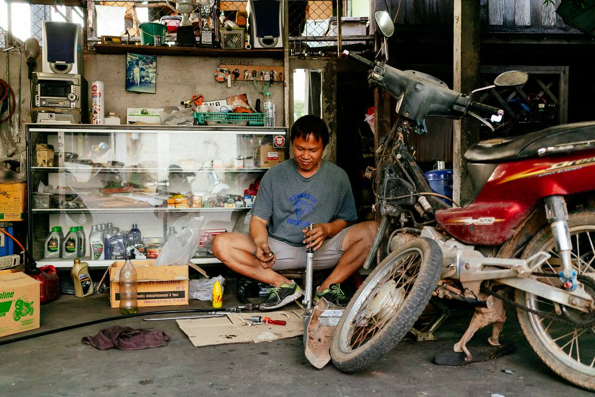 Kleine Werkstatt in Chiang Mai. Handwerker und Motorrad teilen sich wenige Quadratmeter