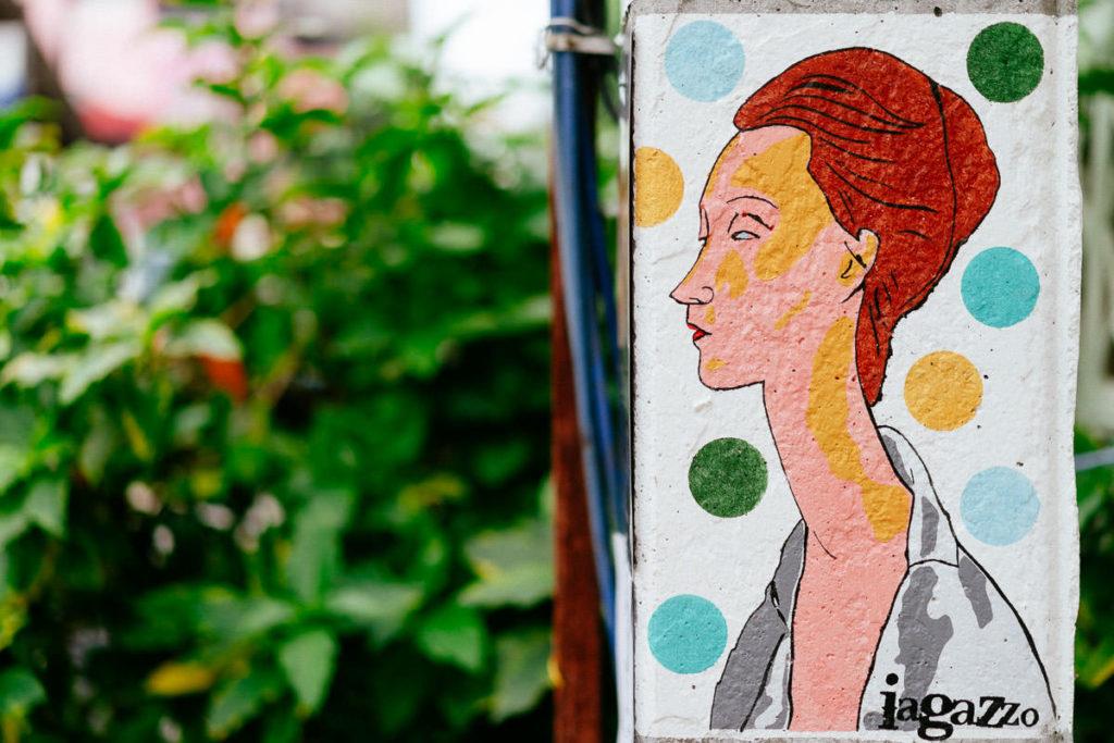 Iagazzo Graffiti einer kurzhaarigen Frau auf weißem Hintergrund mit bunten Punkten