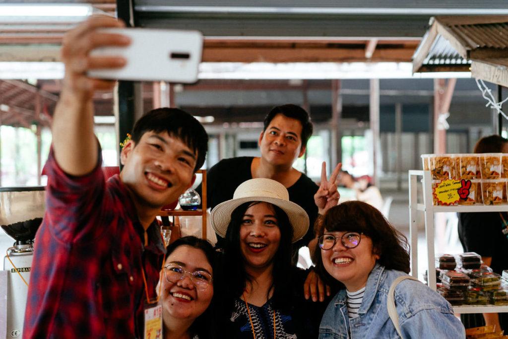 Eine Gruppe von Besuchern und Ausstellern machen ein Selfie auf dem Chiang Mai Coffee Festival
